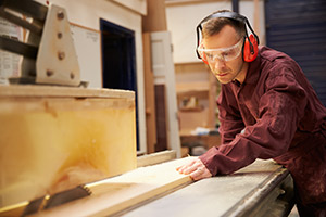 Man using a table saw to cut wood with hearing protection | Omaha NE