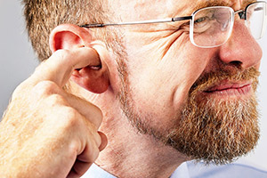 Man cleaning ear with finger - Omaha NE
