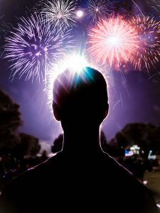 silhouette of a person looking out at fireworks