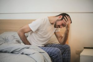 Man sits in bed while holding forehead.